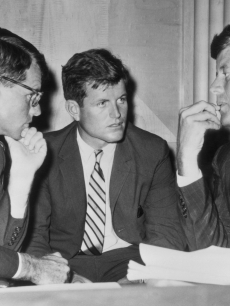 American politician brothers, US attorney-general Robert Kennedy (1925 - 1968), US senator Edward 'Ted' Kennedy, and US president John F. Kennedy (1917 - 1963) speak while seated behind a desk, circa 1962