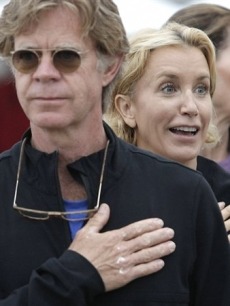 William H. Macy and wife Felicity Huffman look on during the singing of the National Anthem at the Nautica Malibu Triathlon in Malibu, Calif., on September 13, 2009
