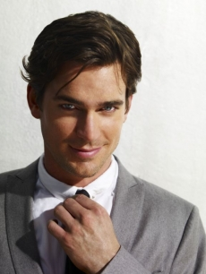 Matt Bomer fixes his tie in a 'White Collar' photo shoot