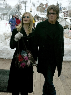 Kyra Sedgwick and Kevin Bacon walk on Main Street during the 2004 Sundance Film Festival on January 19, 2004