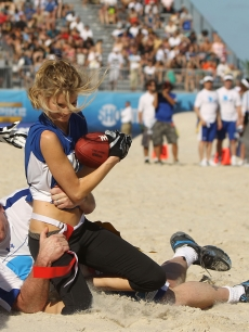 Tom Arnold tackles Marisa Miller during the DIRECTV Celebrity Beach Bowl on February 6, 2010 in Miami Beach, Florida