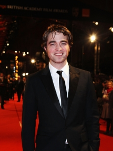 Robert Pattinson makes a smiling appearance on the red carpet at the BAFTA Awards in London, England, on February 21, 2010