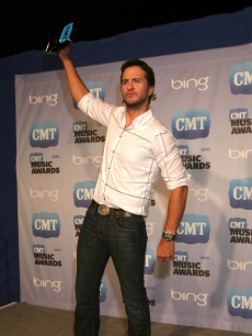Luke Bryan, winner of Breakthrough Video of the Year, raises his trophy in triumph in the CMT Music Awards press room at the Bridgestone Arena in Nashville on June 9, 2010