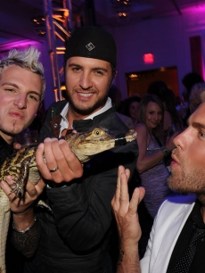 Luke Bryan, Tom Gossin and Mike Gossin of Gloriana play with a baby alligator at the CMT Music Awards after party at the Hutton Hotel in Nashville on June 9, 2010