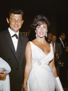 Elizabeth Taylor and her fourth husband American singer and actor Eddie Fisher arrive at a formal event, 1962
