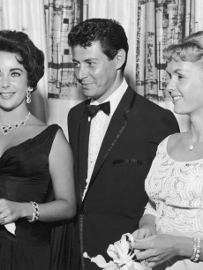 Eddie Fisher, wearing a tuxedo, stands with arm around his wife, Debbie Reynolds and smiles while looking at Elizabeth Taylor, Las Vegas, Nevada, 1958. The next year Fisher left Reynolds and married Taylor