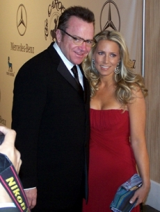 Tom Arnold arrives with his wife, Shelby Roos