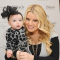 Jessica Simpson rocks her ruby engagement ring while holding a young fan at an in-store appearance at Dillard's Oak Park in Overland Park, Kansas, on November 13, 2010