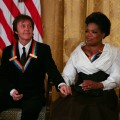 Oprah Winfrey and Paul McCartney listen to President Barack Obama as he gives a speech during the 2010 Kennedy Center Honorees to a reception in the East Room of the White House before going to the Kennedy Center in Washington, DC. on December 5, 2010