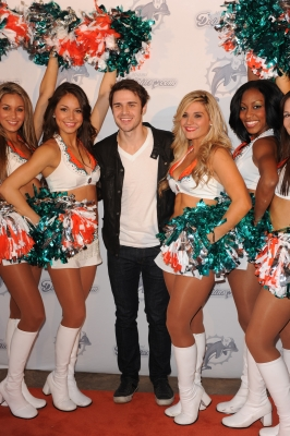 Kris Allen poses with the Dolphin Cheerleaders on the orange carpet at the Miami Dolphins game at Sun Life Stadium in Miami on December 5, 2010