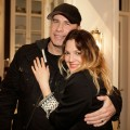 John Travolta and Drew Barrymore hug at an event at producer David Hoberman's home in Brentwood, Calif., on February 10, 2011