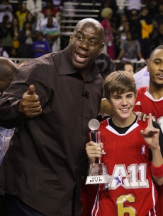 Justin Bieber and Magic Johnson celebrate at the 2011 BBVA NBA All-Star Celebrity Game at the Los Angeles Convention Center in LA on February 18, 2011 