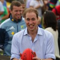 Prince William prepares to kick an AFL ball towards photographers while attending a community BBQ in Murrabit, Australia on March 21, 2011