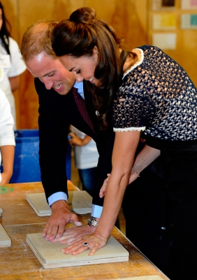 Prince William, Duke of Cambridge, and Catherine, Duchess of Cambridge smile while making hand prints in clay at Inner City Arts in Los Angeles on July 10, 2011