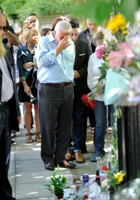 Amy Winehouse's father, Mitch Winehouse, gets emotional as he looks at floral tributes left at her house by fans in London, England on July 25, 2011
