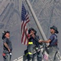 Firefighters raise a U.S. flag at the site of the World Trade Center after two hijacked commercial airliners were flown into the buildings on September 11, 2001 in New York City