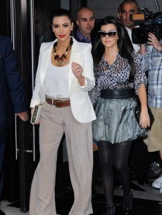 Kim Kardashian and Kourtney Kardashian are surrounded by photographers as they leave their Midtown Manhattan hotel in NYC on October 7, 2011