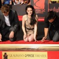 Kristen Stewart gives a smile as she, Robert Pattinson and Taylor Lautner get ready to put their hands in cement in front of Grauman's Chinese Theatre on November 3, 2011 in Hollywood