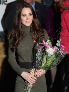 Catherine, Duchess of Cambridge carries a bouquet of flowers during a visit to homeless charity 'Centrepoint' in Camberwell, London, on December 21, 2011