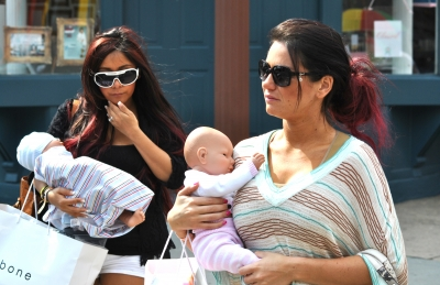 Nicole 'Snooki' Polizzi and Jenni 'JWoww' Farley cradle their baby dolls, seen on location for 'Snooki and JWoww vs. the World' in Jersey City, NJ, on March 23, 2012