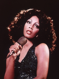 Donna Summer holding a microphone and looking upwards while singing, 1970s