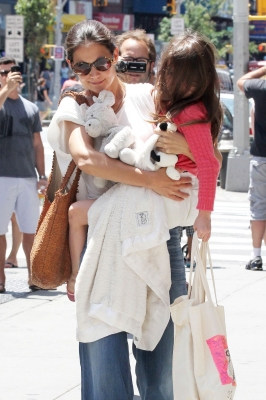 Katie Holmes gives a smile as she carries daughter Suri in New York City on July 8, 2012