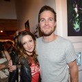 Stephen Amell (R) and Katie Cassidy attend DC Entertainment hosts 'Darkness & Light' party at San Diego Comic-Con International benefitting We Can Be Heroes held at Michael J. Wolf Fine Arts Gallery on July 12, 2012