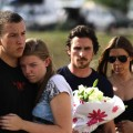 A couple embraces each other as Christian Bale holds flowers with his wife Sandra Blazic before placing them at the memorial in Aurora, Colorado July 24, 2012