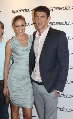 Michael Phelps and 25-year-old model Megan Rossee are seen arm in arm at the Speedo Athlete Celebration at Kensington Roof Gardens in London on August 6, 2012