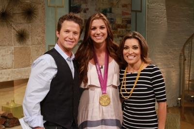 Olympic soccer star Alex Morgan shows off her gold medal with Billy Bush and Kit Hoover on Access Hollywood Live on August 28, 2012