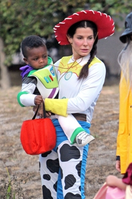 Sandra Bullock takes on 'Toy Story' as cowgirl Jessie, and totes around her own Buzz Lightyear son Louis, as they celebrate Halloween in Los Angeles on October 31, 2012