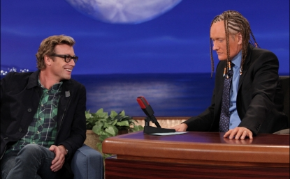 Guest Simon Baker of 'The Mentalist' marvels at Conan O'Brien's cornrows and spray tan on 'Conan,' Oct. 25, 2012