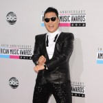 Psy shows off some Gangman style dance moves as he walks the red carpet of the 40th American Music Awards at Nokia Theatre on November 18, 2012 in Los Angeles