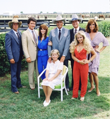 A promotional still from the American television series 'Dallas' shows the cast assembled on the property of the Southfork ranch, on the outskirts of Dallas, Texas, 1979. From left, American actors Steve Kanaly (as Ray Krebbs), Patrick Duffy (as Bobby Ewing), Victoria Principal (as Pamels Barnes Ewing), (sitting), Barbara Bel Geddes (as Eleanor Southworth 'Miss Ellie' Ewing), Jim Davis (1909 - 1981) (as John Ross 'Jock' Ewing), Larry Hagman (as John Ross 'J.R.' Ewing, Jr.), Charlene Tilton (as Lucy Ewing) (in red), and Linda Gray (as Sue Ellen Ewing)