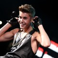 Justin Bieber shows off his guns while onstage during Hot 99.5's Jingle Ball 2012 on December 11, 2012 in Washington, D.C.