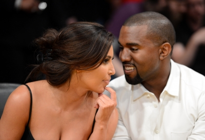 Kim Kardashian and rapper Kanye West talk from their courtside seats before the Los Angeles Lakers take on the Denver Nuggets in Game Seven of the Western Conference Quarterfinals in the 2012 NBA Playoffs on May 12, 2012 at Staples Center in Los Angeles