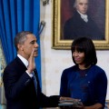 President Barack Obama takes the oath of office as first lady Michelle Obama holds the Bible in the Blue Room of the White House January 20, 2013 in Washington, DC