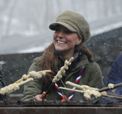 Catherine, Duchess of Cambridge cooks dough around a campfire at the Great Tower Scout camp on March 22, 2013 in Windermere, Cumbria, United Kingdom