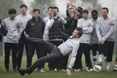 David Beckham falls during his visit to Wuhan Zall Football club on March 23, 2013 in Wuhan, Hubei Province of China