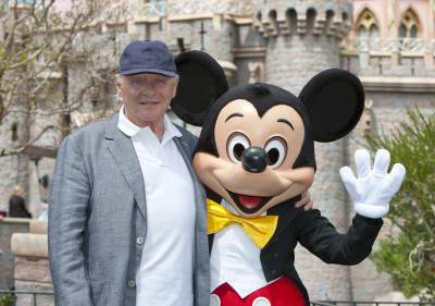 Sir Anthony Hopkins meets Mickey Mouse in front of Sleeping Beauty Castle at Disneyland park in Anaheim, Calif., on April 1, 2013