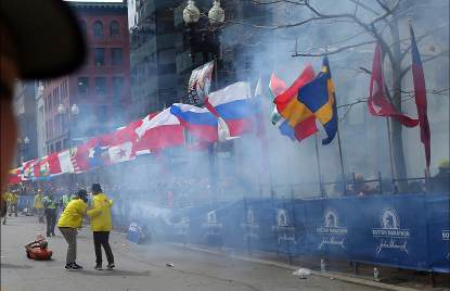 Officials react as the first explosion goes off on Boylston Street near the finish line of the 117th Boston Marathon on April 15, 2013