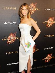 Jennifer Lawrence looks stunning in a white dress and pink heels at Lionsgate&#8217;s &#8216;The Hunger Games: Catching Fire&#8217; Cannes Party at Baoli Beach sponsored by Covergirl on May 18, 2013 in Cannes, France