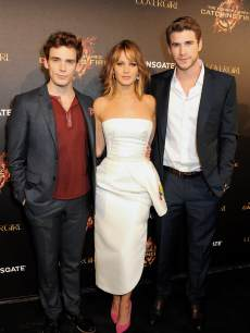 Sam Claflin, Jennifer Lawrence and Liam Hemsworth are seen at Lionsgate&#8217;s &#8216;The Hunger Games: Catching Fire&#8217; Cannes Party at Baoli Beach sponsored by Covergirl on May 18, 2013 in Cannes, France