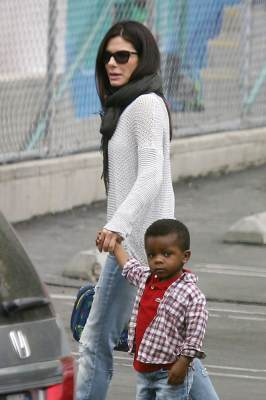 Sandra Bullock leads her son Louis into his school in Los Angeles on May 21, 2013