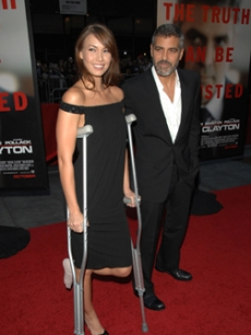 George Clooney escorts girlfriend Sarah Larson who is on crutches