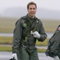 Prince William gestures as he walks across the airfield at the RAF Cranwell training school in Lincolnshire, England