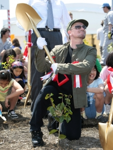 Bono plants a tree at a 'Green Island' event in Tokyo, Japan