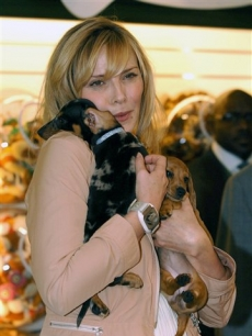 Kim Cattrall and miniature smooth coat dachshunds at the Harrods Summer Sale in Knightsbridge