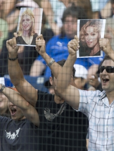 Fans hold up pictures of Madonna as Alex Rodriguez strikes out in Canada