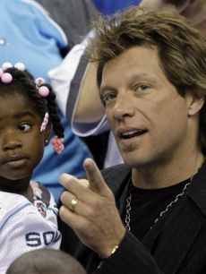 Jon Bon Jovi and a fan catch the ArenaBowl XXII football game